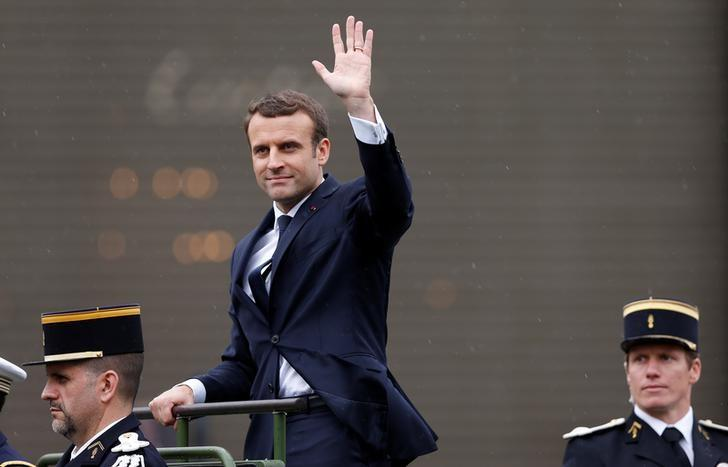 French President Emmanuel Macron waves from a command car on the Champs Elysees avenue after the handover ceremony in Paris, France, May 14, 2017.      REUTERS/Francois Lenoir