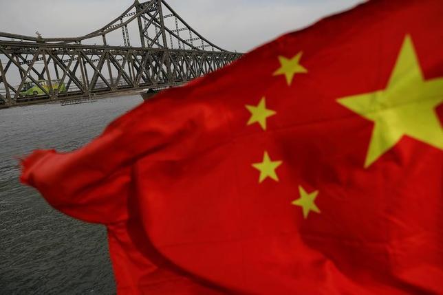 5月15日、中国の習近平国家主席は、中国が進めるシルクロード経済圏構想「一帯一路」の国際会議で、「一帯一路」が保護主義を拒否し、分裂を回避する必要があると述べた。写真は中国国旗と、遼寧省丹東市─北朝鮮新義州市を結ぶ中朝友誼橋。4月撮影(2017年 ロイター/Damir Sagoj)
