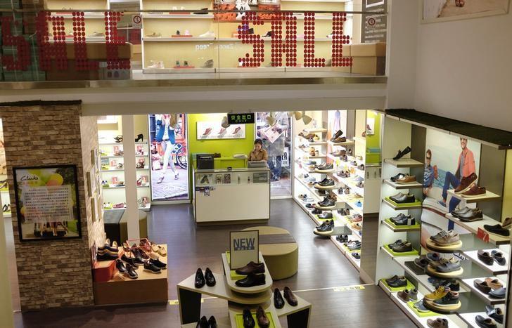 资料图片:2013年8月,北京一家购物中心内鞋店的销售员等待顾客上门。REUTERS/Jason Lee