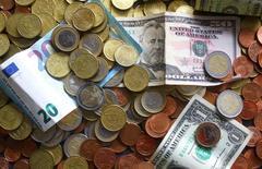 Доллары и евро. Доллар начал неделю в обороне после выхода экономических данных США, которые не оправдали прогнозы, а также из-за очередного ракетного испытания КНДР на минувших выходных.  REUTERS/Kai Pfaffenbach