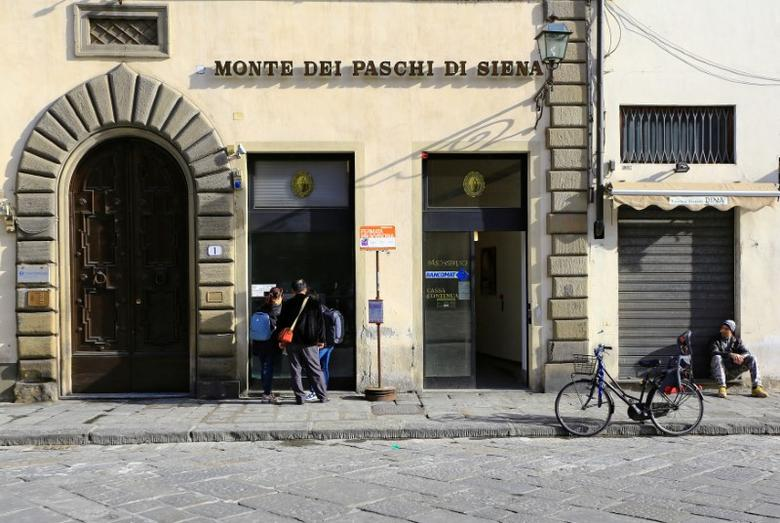 FILE PHOTO: People use a cash machine of Monte Dei Paschi bank in downtown in Florence, Italy March 1, 2016. REUTERS/Tony Gentile/File photo