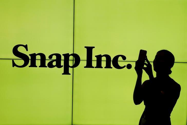 A woman stands in front of the logo of Snap Inc. on the floor of the New York Stock Exchange (NYSE) while waiting for Snap Inc. to post their IPO, in New York City, New York, U.S. on March 2, 2017. REUTERS/Lucas Jackson/Files