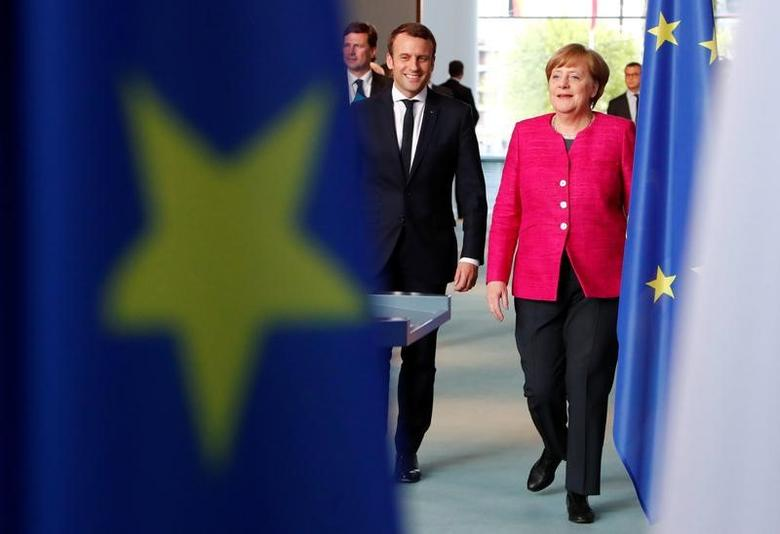 German Chancellor Angela Merkel and French President Emmanuel Macron arrive to a news conference at the Chancellery in Berlin, Germany, May 15, 2017.   REUTERS/Fabrizio Bensch/Files