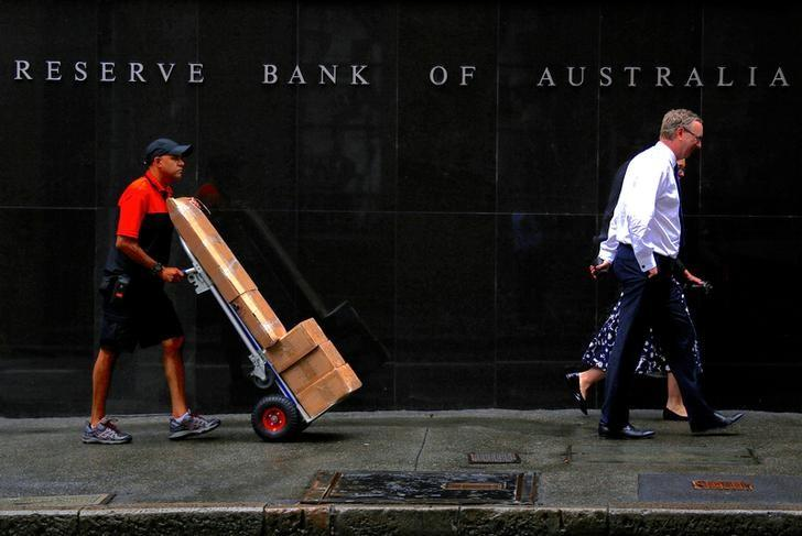 A worker pushing a trolley walks with pedestrians past the Reserve Bank of Australia (RBA) head office in central Sydney, Australia, March 7, 2017. REUTERS/David Gray/Files