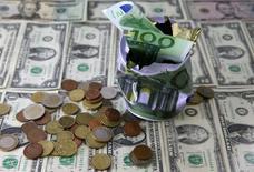 Доллары и евро. Евро коснулся недельного пика во вторник в преддверии выхода данных о ВВП еврозоны, тогда как доллар оказался под давлением из-за неожиданно слабых данных о промпроизводстве в США. REUTERS/Dado Ruvic/Illustration