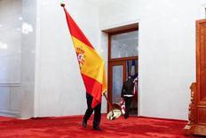 El Tesoro español colocó el martes 1.605 millones de euros en deuda a corto plazo y a tipos negativos en los dos plazos ofrecidos.  En la imagen, un funcionario traslada una bandera española durante la visita oficial del presidente del Gobierno, Mariano Rajoy, a China el 13 de mayo de 2017. REUTERS/Thomas Peter