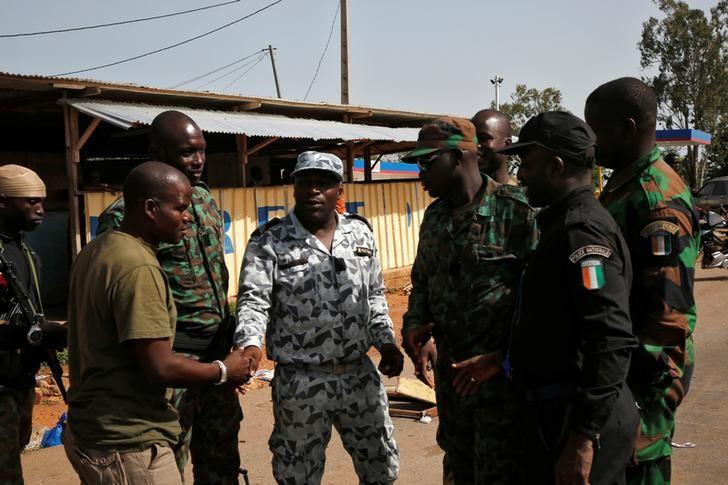Mutinying soldiers shake hands with Ivory Coast's National Police officer as they prepare to leave the checkpoint at the entrance to Bouake, Ivory Coast, May 16, 2017. REUTERS/Luc Gnago