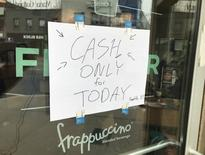 A sign informing customers that electronic payments are not functioning is seen at the entrance of a Starbucks coffee shop in Toronto, Ontario, Canada May 16, 2017.   REUTERS/Chris Helgren