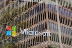 An promotional video plays behind a window reflecting a nearby building at the Microsoft office in Cambridge, Massachusetts, U.S. May 15, 2017. REUTERS/Brian Snyder