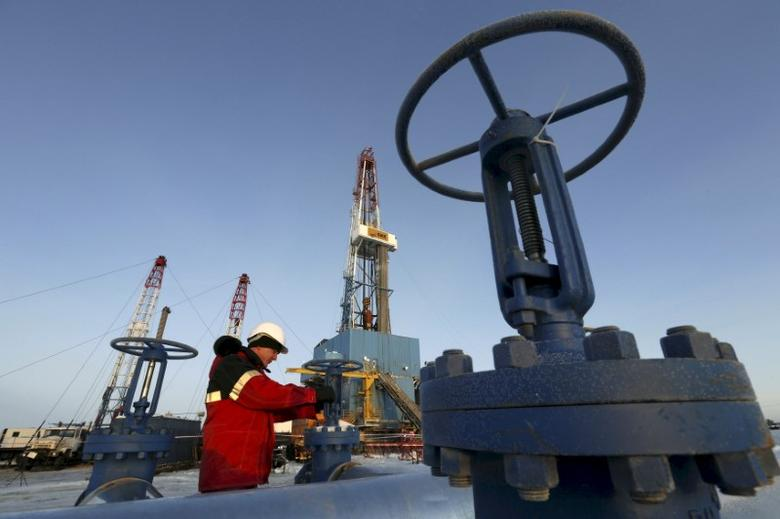 FILE PHOTO: A worker checks a valve of an oil pipe at the Lukoil company owned Imilorskoye oil field outside the West Siberian city of Kogalym, Russia, in this January 25, 2016 file photo.   REUTERS/Sergei Karpukhin/File Photo