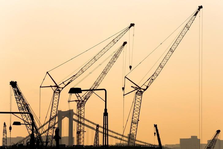 Cranes are pictured against the sunset at construction site in the Toyosu district in Tokyo, February 12, 2015.REUTERS/Thomas Peter/File Photo