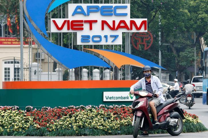 2017年5月17日,越南河内, 一名骑摩托车的人停在一处APEC峰会宣传标识旁边。REUTERS/Kham