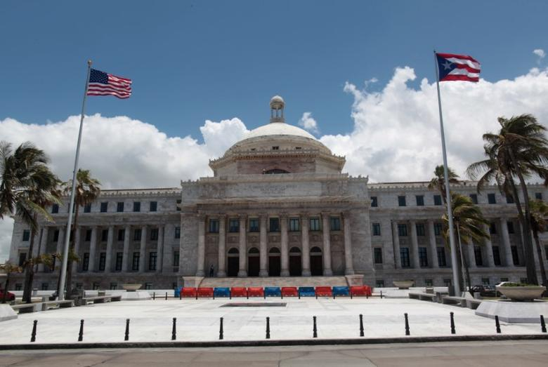 The flags of the U.S. and Puerto Rico fly outside the Capitol building in San Juan, Puerto Rico May 4, 2017. REUTERS/ Alvin Baez