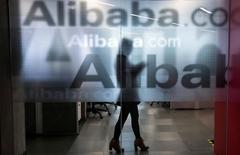 An employee is seen behind a glass wall with the logo of Alibaba at the company's headquarters on the outskirts of Hangzhou, Zhejiang province, April 23, 2014.  REUTERS/Chance Chan/File Photo                  GLOBAL BUSINESS WEEK AHEAD PACKAGE - SEARCH 'BUSINESS WEEK AHEAD 31 OCT'  FOR ALL IMAGES