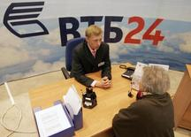 An employee of VTB, Russia's second-largest bank, talks to a customer at a bank office in central Moscow April 27, 2007. VTB will try to raise up to $8.4 billion in an initial public offering (IPO) in London next month, seeking to almost match rival Sberbank's $8.95 billion rights issue. REUTERS/Alexander Natruskin  (RUSSIA)