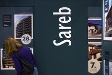 El denominado banco malo español analiza una eventual colocación en bolsa de parte de sus activos dentro de una socimi, un tipo de vehículo inmobiliario que está viviendo un momento dulce en España, según dijo el jueves el ministro de Economía. En la imagen de archivo, una clienta mirando anuncios en el stand de la Sareb en una feria inmobiliaria en Madrid, el 30 de mayo de 2013. REUTERS/Sergio Pérez