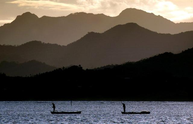 FILE PHOTO: Fijian fishermen stand in their boats as they work in front of an island's mountain range near Suva April 29, 2004. REUTERS/David Gray/File Photo