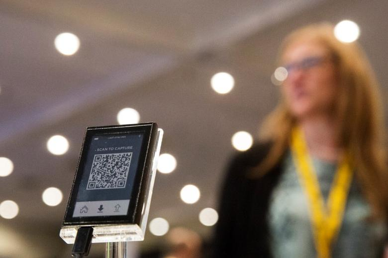 A woman stands behind a digital Bitcoin wallet during the Inside Bitcoins: The Future of Virtual Currency Conference in New York April 8, 2014. REUTERS/Lucas Jackson