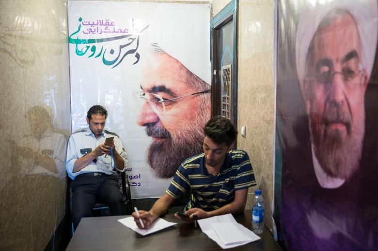 FILE PHOTO: Men use their smartphones to follow election news as posters of Iran's President Hassan Rouhani are seen in Tehran, Iran May 17, 2017. REUTERS/TIMA
