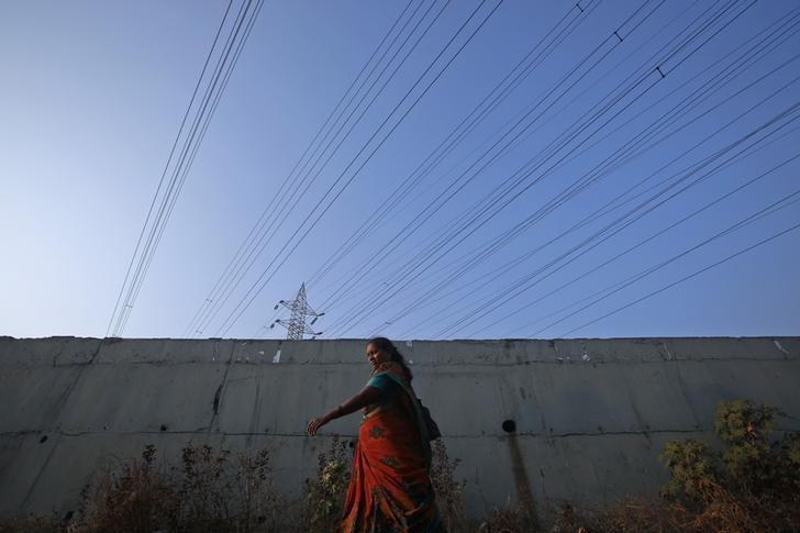 A woman walks under high-tension power lines leading from a Tata Power sub station in Mumbai's suburbs February 10, 2013. REUTERS/Vivek Prakash/Files