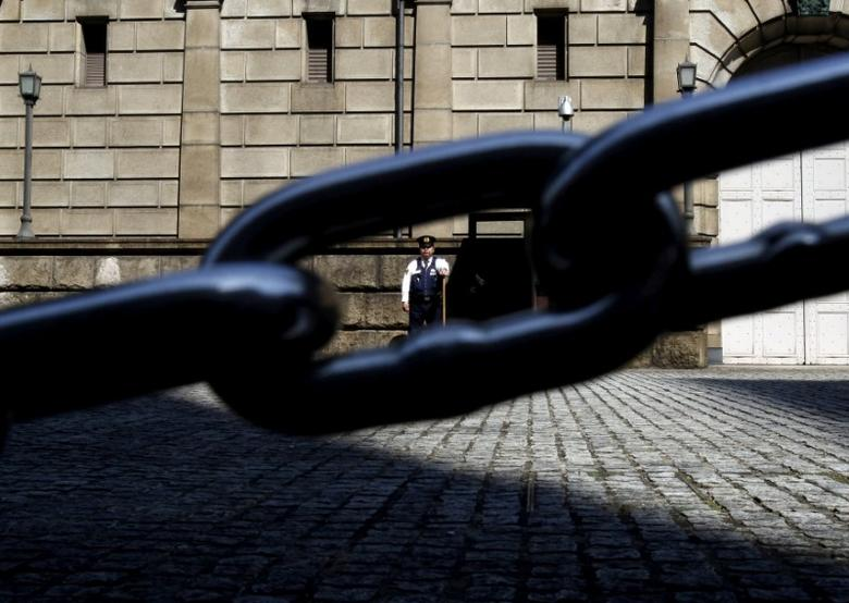 FILE PHOTO: A security officer is seen through a chain link as he stands guard outside the Bank of Japan headquarters in Tokyo, Japan, March 31, 2016. REUTERS/Yuya Shino/File Photo