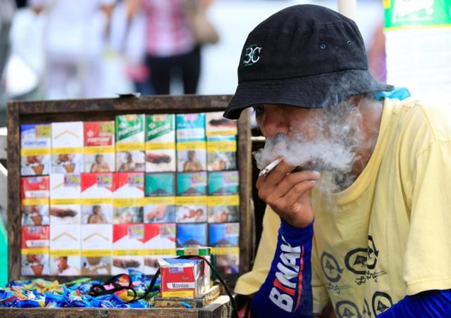 A vendor smokes beside his cigarette stall, while waiting along a main street, in metro Manila, Philippines May 19, 2017. REUTERS/Romeo Ranoco