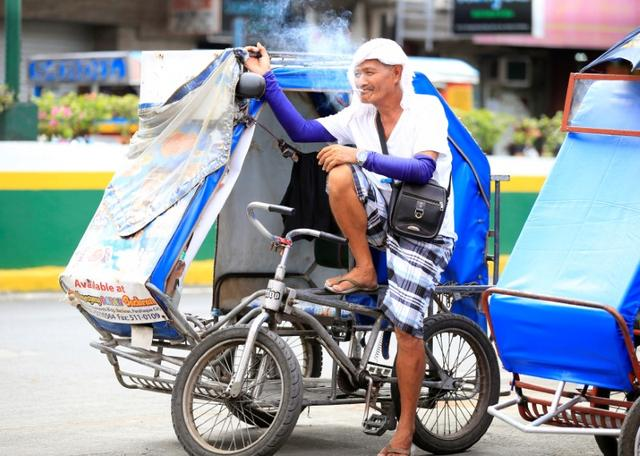 A tricycle taxi driver smokes cigarette, while taking a break along a main street, in metro Manila, Philippines May 19, 2017. REUTERS/Romeo Ranoco