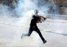 محتج فلسطيني يقذف حجرا صوب قوات إسرائيلية خلال اشتباكات في بيت لحم بالضفة الغربية يوم الجمعة. تصوير: عمار عوض - رويترز.