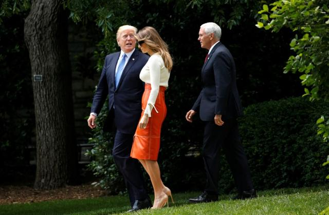 U.S. President Donald Trump looks back toward his wife Melania and Vice President Mike Pence as he departs the White House to embark on a trip to the Middle East and Europe in Washington, U.S., May 19, 2017. REUTERS/Kevin Lamarque
