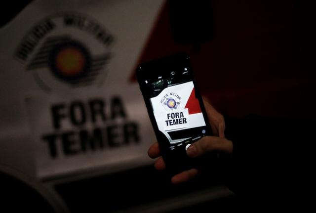 A demonstrator takes a picture of a sign reading ''Out Temer'' on a military police car during a protest against Brazil's President Michel Temer in Sao Paulo, Brazil, May 18, 2017. REUTERS/Nacho Doce