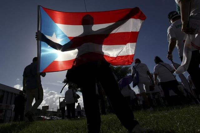 FILE PHOTO - A protester holding a Puerto Rico's flag takes part in a march to improve healthcare benefits in San Juan, Puerto Rico, November 5, 2015. REUTERS/Alvin Baez