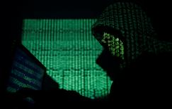 FILE PHOTO: A hooded man holds a laptop computer as cyber code is projected on him in this illustration picture taken on May 13, 2017. REUTERS/Kacper Pempel/Illustration