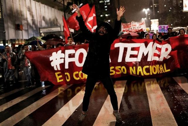 Demonstrators take part in a protest against Brazil's President Michel Temer in Sao Paulo, Brazil, May 18, 2017. The banner reads ''Out Temer.'' REUTERS/Nacho Doce