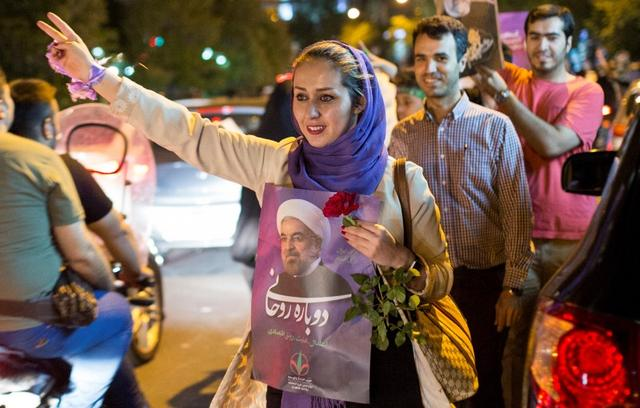 A woman holds a poster of Iranian President Hassan Rouhani during a campaign rally in Tehran, Iran, May 17, 2017. TIMA via REUTERS