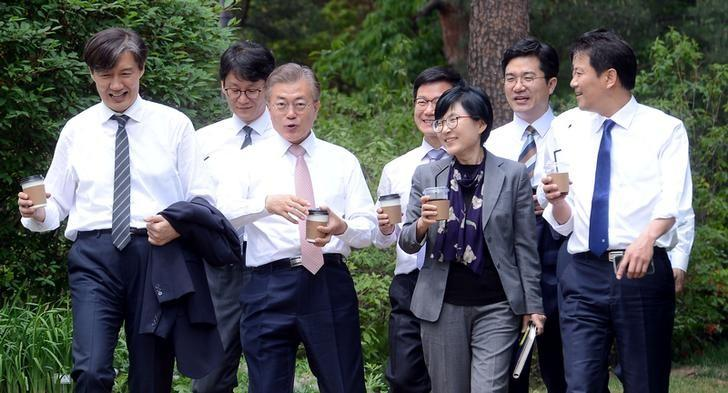South Korean President Moon Jae-in takes a walk with senior presidential secretaries at the Presidential Blue House in Seoul, South Korea, May 11, 2017. Yonhap via REUTERS