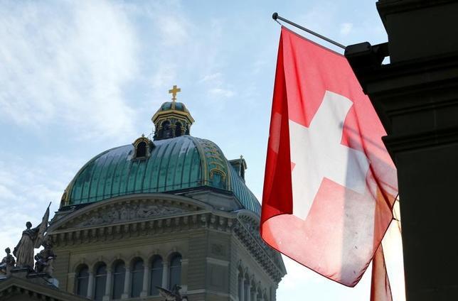 5月21日、スイスで、原発の新設を禁止し、風力や太陽光、水力などの再生可能エネルギーを推進する新法の是非を問う国民投票が行われ、賛成多数で可決された。写真はスイスの連邦議事堂とスイス国旗。ベルンで1月撮影(2017年 ロイター/Denis Balibouse)