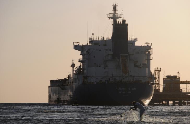 资料图片:2013年4月,沙特西北部港口杜巴,一名渔民在港口停泊的油轮附近收网。REUTERS/Mohamed Al Hwaity
