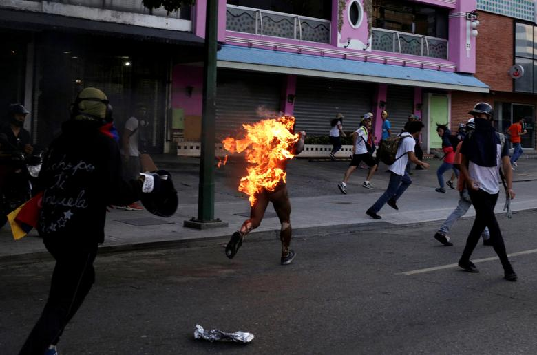 A man who was set on fire by people accusing him of stealing during a rally against Venezuela's President Nicolas Maduro runs amidst opposition supporters in Caracas, Venezuela, May 20, 2017. REUTERS/Marco Bello