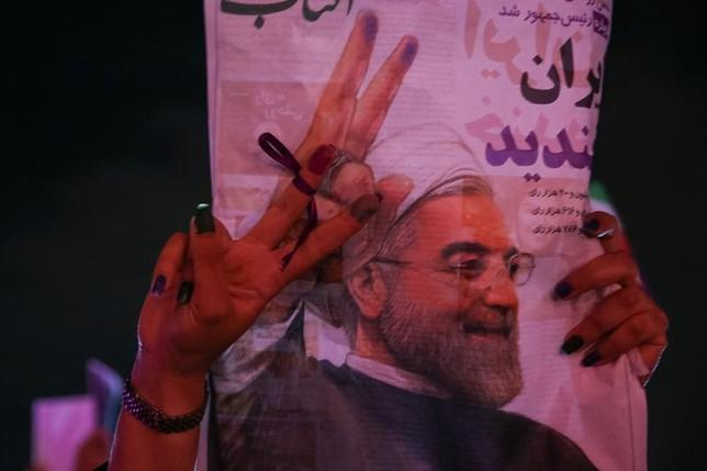 5月19日、イラン大統領選は、穏健派で現職のロウハニ師が再選を決めたが、保守強硬派は敗北の借りを返そうとロウハニ師の政策に抵抗し続けるとみられ、両者の対立が激化しそうだ。写真は、ロウハニ師のポスターを掲げる支持者。テヘランで20日撮影。提供写真(2017年 ロイター/TIMA via REUTERS)