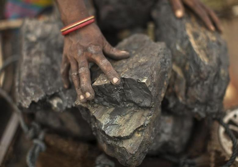 FILE PHOTO: A local woman prepares to carry coal at an open coal field at Dhanbad district in the eastern Indian state of Jharkhand September 19, 2012. REUTERS/Ahmad Masood/Files