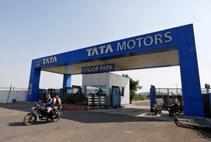 FILE PHOTO: Men ride a motorbike past a Tata Motors car plant at Sanand, in the western Indian state of Gujarat, October 27, 2016. REUTERS/Amit Dave/File photo