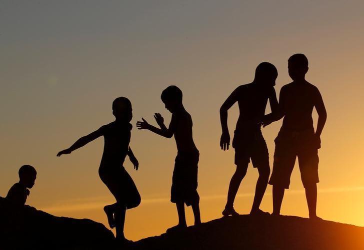 资料图片:2016年12月,南方开普敦Camps湾海滩,孩子们在裸露的岩石上玩耍。REUTERS/Mike Hutchings