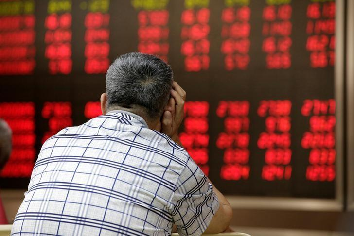 FILE PHOTO - An investor looks at an electronic board showing stock information at a brokerage house in Beijing, China, June 24, 2016. REUTERS/Jason Lee