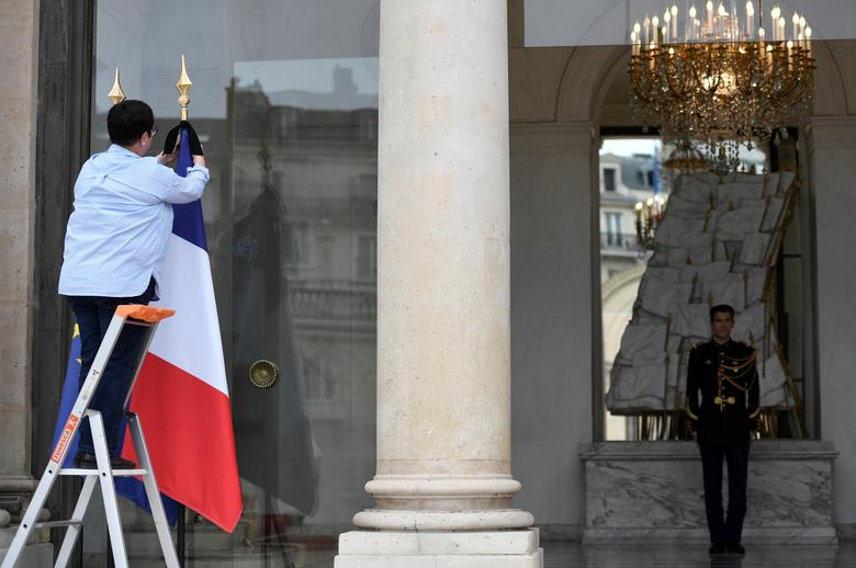 An employee ties a black ribbon on a French flag at the Elysee Palace in Paris, France, May 24, 2017 to mourn the victims of the Manchester attack. REUTERS/Stephane De Sakutin/Pool