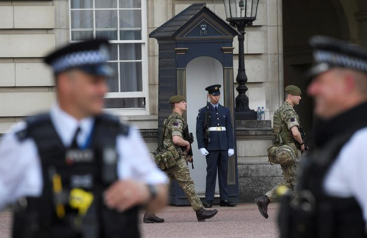 Soldiers walk behind police officers in the grounds of Buckingham Palace in London, Britain May 24, 2017. REUTERS/Neil Hall
