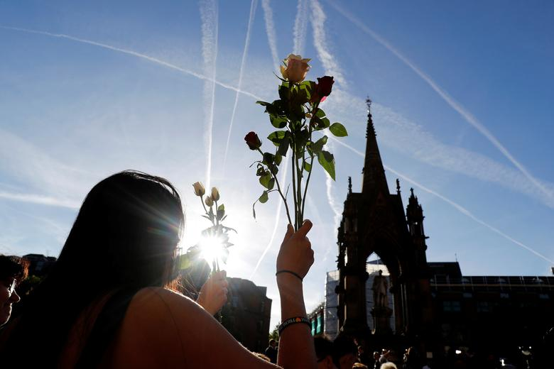 A woman holds flowers as she takes part in a vigil in central Manchester. REUTERS/Darren Staples
