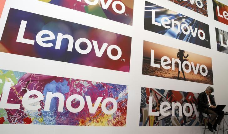 A man uses his laptop next to Lenovo's logos during the Mobile World Congress in Barcelona, Spain February 25, 2016. REUTERS/Albert Gea/Files