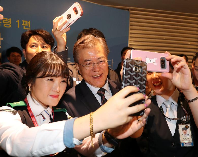 FILE PHOTO: Employees take a selfie with South Korean President Moon Jae-in at the Incheon International Airport in Incheon, South Korea, May 12, 2017.   Yonhap via REUTERS