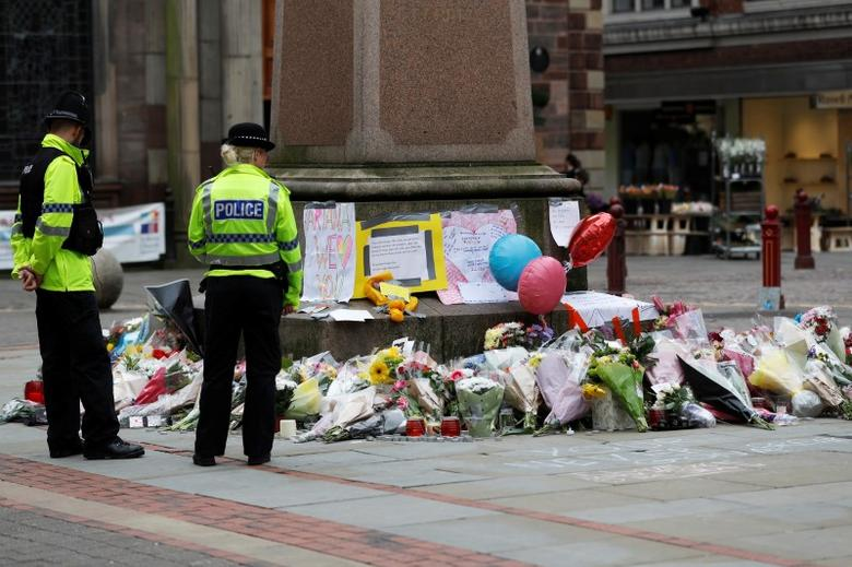 Police officers stand next to floral tributes left for the victims of an attack on concert goers at Manchester Arena, in St Ann's Square, in Manchester, Britain May 24, 2017. REUTERS/Peter Nicholls