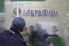 Мужчина моет окна в офисе Мегафона в Москве 28 ноября 2012 года. Чистая прибыль российского телекоммуникационного оператора Мегафон в первом квартале 2017 года упала более чем вдвое до 4,2 миллиарда рублей в основном из-за более высоких убытков по курсовым разницам и увеличения расходов на обслуживание кредитов в связи с займом, который компания взяла под сделку с Mail.ru, сообщил Мегафон в четверг. REUTERS/Sergei Karpukhin